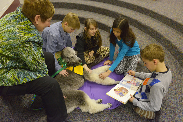 Globe/Roger Nomer<br /> (from left) Sue Hicks, Thomas Jefferson fifth graders Noah Hamlett, Olivia Staso, Sonia Carlson and Matthias Laurey read to Colt during the school's Read Across America event on Thursday morning.