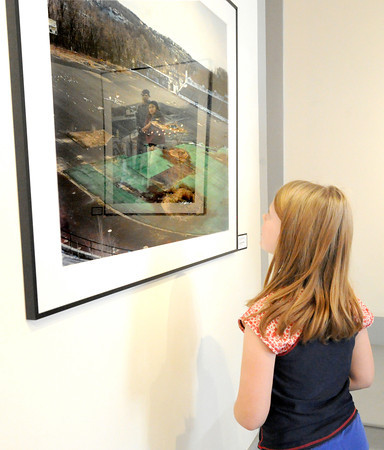 "Another entry is reflected onto a photograph entitled ""Hinchcliffe Stadium"" by Brooklyn photographer Michael Joseph Dalton as Willow Donehue, 9, of Ardmore, Okla., examines the art on Friday at Spiva. Donehue, formerly of Joplin, decided to spend part of her Spring Break at Spiva.<br /> Globe 