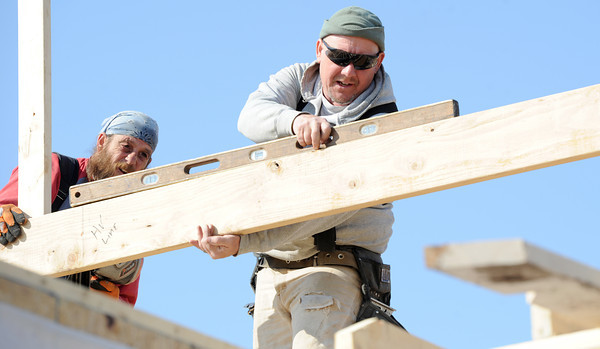 Mike Hartman, left and Todd Mitts of Woodchuck Custom Framing build gables on the roof of a new home being constructed by Ledford Construction at 2018 South Florida on Thursday. <br /> Globe | Laurie Sisk