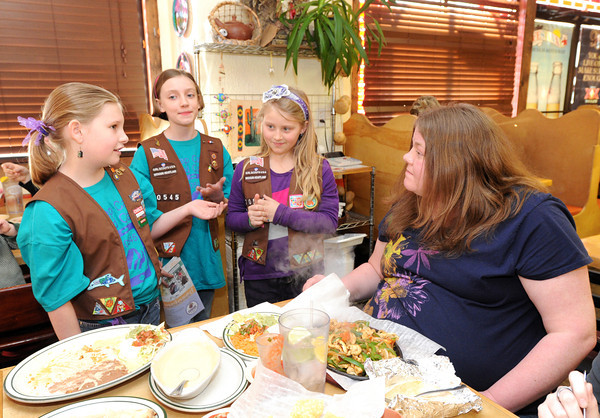 Nine-year-old Girl Scout Brooklyn Hiller, left explains to Festival Mexican Restaurant customer Brandi Fry, right,  how the Girl Scouts are working to raise money for improvements at Camp Mintahama. Also pictured are Nine-year-olds Deya Yandell, second from the left and Brynlee Hollingsworth. About 10 restaurants kicked in a portion of their proceeds Wednesday night to help the scouts.<br /> Globe | Laurie Sisk