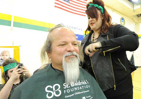 Janelle Jacobson, of City Pointe Beauty Academy, shaves the head of Missouri Southern business professor Scott Cragin during the St, Baldrick event on Wednesday night at MSSU's Robert Ellis Young Gymnasium. Cragin raised about $2,000 to benefit the St. Baldrick's Foundation, which works to conquer childhood cancer.<br /> Globe | Laurie Sisk