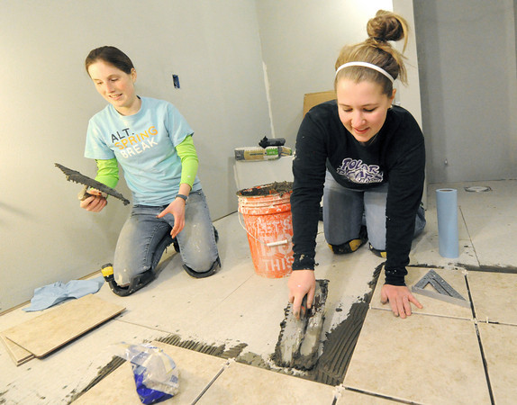 Krissy Piotroski, left and Hanna Richwine lay ceramic tiles in the bathroom of a Rebuild Joplin home at 2018 Annie Baxter on Wednesday.<br /> Globe | Laurie Sisk