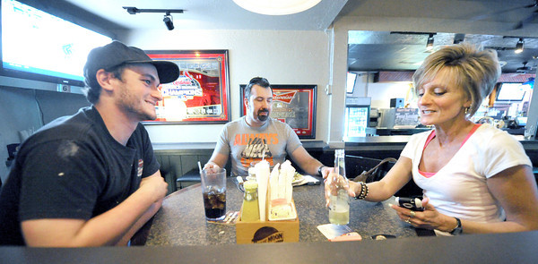 From the left: Matthew Gilliam, Chris Greninger and Carol Brockman enjoy food and drink inside the now smoke free Kitchen Pass restaurant. Brockman said she stopped patronizing the establishment because of the persistant odor of smoke, but was delighted to hear the business had gone smoke free.<br /> Globe | Laurie Sisk