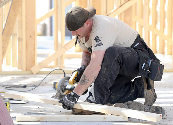 Joel Haggard, of Woodchuck Custom Framing cuts boards for gables for the roof of a new home being constructed by Ledford Construction at 2018 South Florida on Thursday. <br /> Globe | Laurie Sisk