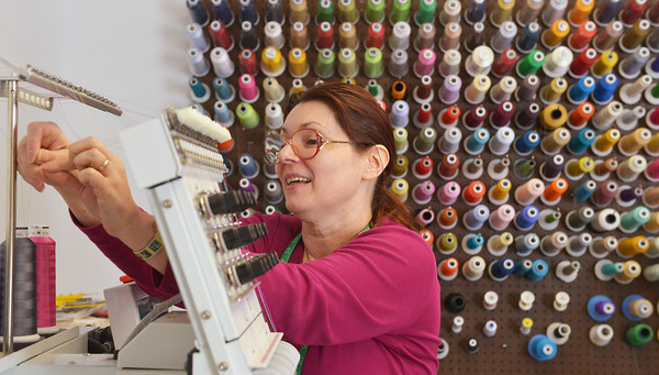 Globe/Roger Nomer<br /> Ukraine native Liliya Moos threads a machine at Adornables on Monday morning.
