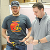 Pittsburg State University seniors Austin Leake, left and Cody Frieden discuss the advantages of snappable hinges on Thursday at the Kansas Technology Center.<br /> Globe | Laurie Sisk