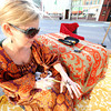 Jenifer Hall, of Kansas City's Sephirot Henna, applies a henna tatoo to her hand while waiting for the crowds to arrive at the first Third Thursday of the season on Main street.<br /> Globe | Laurie Sisk