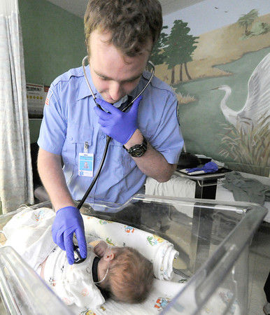 Crowder College international paramedic student Ian Kearney, of Dublin, Ireland tends to 15-day-old Cooper DeShields on Wednesday at Freeman West Hospital.<br /> Globe | Laurie Sisk