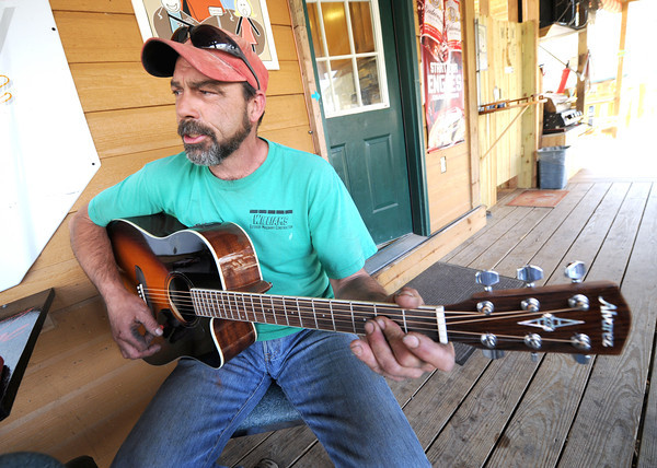 Kelly Williams, a regular at River's Bend, plays a song for fellow patrons of the establishment on Tuesday night. The bar and grill also has an inside music room for guests who want to play their music.<br /> Globe | Laurie Sisk