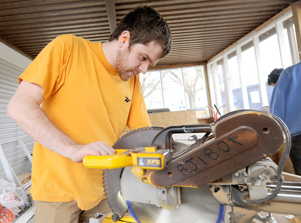 University of Connecticut student T.J. Green suts laminate for floors while working on a house at 2018 Annie Baxter on Wednesday. Green is one of about 20 Connecticut students spending their Spring Break helping Rebuild Joplin.<br /> Globe | Laurie Sisk