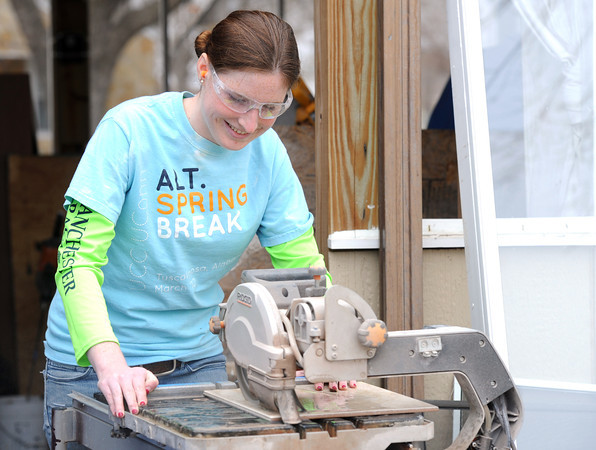 Krissy Piotroski cuts ceramic tiles for the bathroom of a Rebuild Joplin home at 2018 Annie Baxter on Wednesday.<br /> Globe | Laurie Sisk