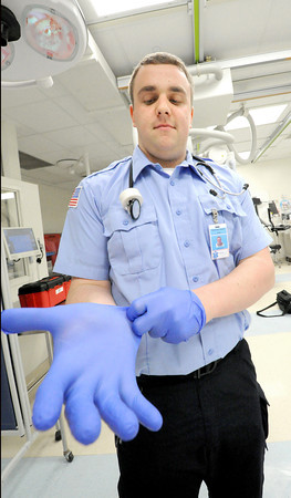 "Crowder College international paramedic student John Barron ""gloves up""  on Wednesday in the emergency room at Freeman West Hospital.<br /> Globe 