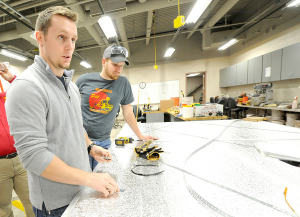Pittsburg State seniors Cody Frieden and Austin Leake discuss the advantage of snap together hinges on  their rapidly deployed shelter on Thursday at the Kansas Technology Center.<br /> Globe | Laurie Sisk