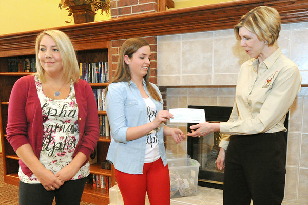 Members of Pittsburg State University's Chapter of Alpha Sigma Alpha Madalyn Overstreet, left and Hannah Wooten, center, present a check for $1,204 to Tara Horinek, associate drector for Ronald McDonald House Charities on Wednesday at the house. Alpha Sigma Alpha members, along with men from Sigma Tau Gamma raised the money through at 72-hour Swing-A_Thon on the PSU campus.<br /> Globe | Laurie Sisk