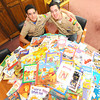 Fifteen-year-old Nathan Salyer, left and 17-year-old Zach Salyer sit near the hundreds of books they have collected and plan to donate to NALA.<br /> Globe | Laurie Sisk