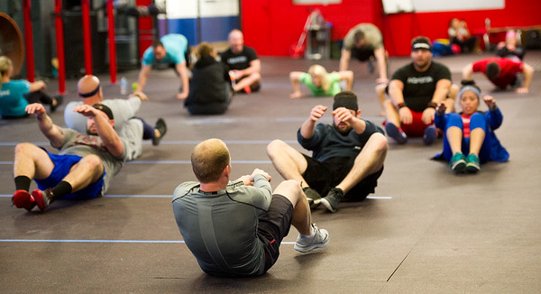 Members work out during a cross fit class on Tuesday at Midwestern Built.<br /> Globe | Laurie Sisk