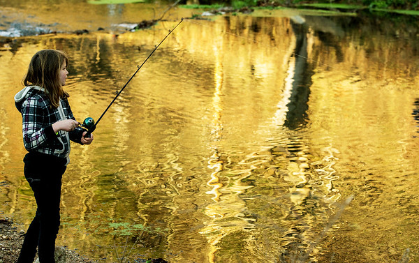 Globe/Roger Nomer<br /> As the rising sun is reflected in Roaring River, Kayla Hendrix, 10, Washburn, fishes on Wednesday at the state park.