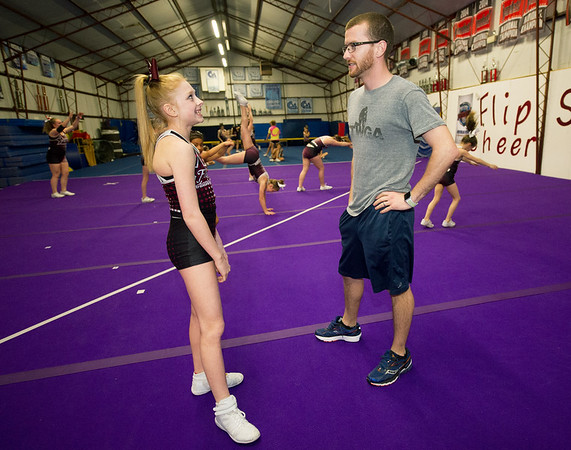 Sean Haase chats with 12-year-old Avinee Jones during practice at the Flip Shop Cheer Zone in Webb City  on March 16. In addition to coaching the girls, Haase also flies a medical helicopter.<br /> Globe | Laurie Sisk