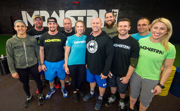 Midwestern Built partner Jason Ansley, center and his wife Heidi Ansley join their Midwestern Built coaches for a photo on Wednesday at the cross fit gym.<br /> Globe | Laurie Sisk