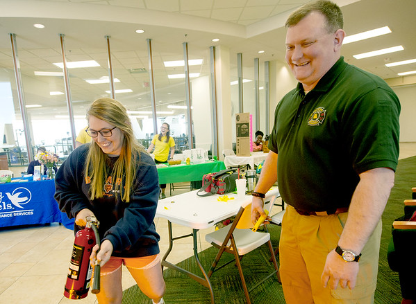 From the left: Missouri Southern student Allison Anth, of St. Louis, learns how to use a fire extinguisher quickly and efficiently under the watchful eye of Christopher Houk, coordinator for fire, safety and environmental health at MSSU during the MSSU 7th Annual Wellness Expo on Wednesday at the Billingsley Student Center.<br /> Globe | Laurie Sisk