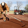Webb City Parks and Recreation worker Tony Bass on Friday spreads new crushed lava on the Farm Club field at King Jack Park in preparation for the start of youth baseball.<br /> Globe | Laurie Sisk