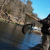 Globe/Roger Nomer<br /> Chris Jasum, Pierce City, fishes his lunker out of the river with a net on Wednesday during opening day at Roaring River State Park.