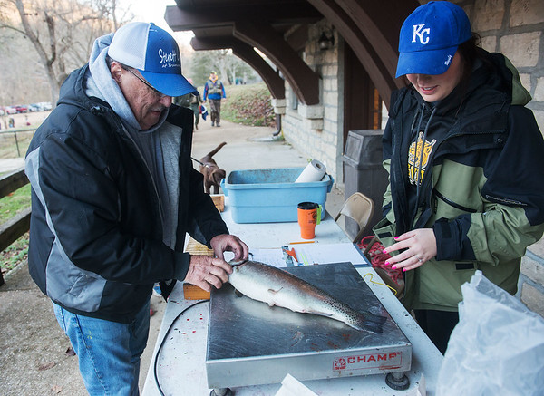 Globe/Roger Nomer<br /> Brittany Farris, director of the Cassville Chamber of Commerce, weighs Chuck Martin's catch on Wednesday during opening day at Roaring River State Park.