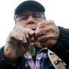Globe/Roger Nomer<br /> James Pippin, Seligman, ties on a fly on Wednesday during opening day at Roaring River State Park.