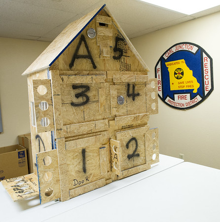 "A ""burn house,"" built by Carl Junction Fire Department volunteer Paul Merwin, sits inside the department last week. According to Chief Joe Perkins, the house would cost about $1,000 to purchase and is an example of some of the things volunteers contribute through their individual talents. Merwin is an engineer for Tamko when he is not volunteering for the department.<br /> Globe 