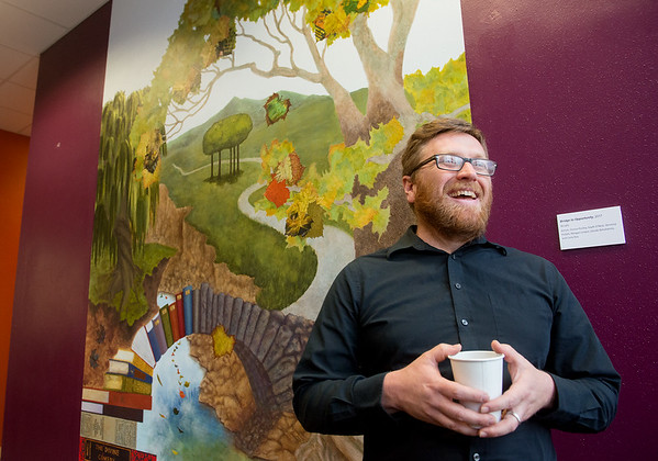 Globe/Roger Nomer<br /> Kyle McKenzie, assistant professor at Missouri Southern, talks about the student-created mural in Spiva Library on Monday.