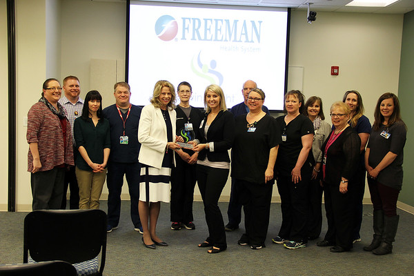 Photo Courtesy Freeman Health System<br /> Surrounded by members of Freeman Donor Council, Paula F. Baker, Freeman President and Chief Executive Officer, accepts the Excellence in Eye Donation Award from Haley Lyne, Saving Sight Partner Relations Coordinator on Wednesday at Freeman Hospital West. This award recognizes achievements in providing the gift of sight through corneal transplants.