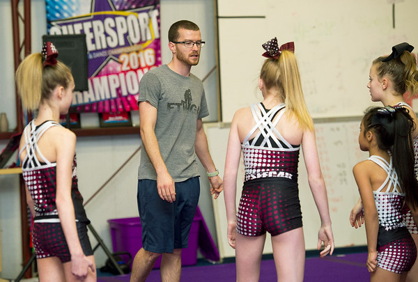 Sean Haase works with girls at the Flip Shop Cheer Zone in Webb City  on March 16. In addition to coaching the girls, Haase also flies a medical helicopter.<br /> Globe | Laurie Sisk