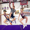 Sean Haase, center, executes a heel kick with Maggie Brown, 14, left and Avinee Jones, 12, right, during practice at the Flip Shop Cheer Zone in Webb City  on March 16. In addition to coaching the girls, Haase also flies a medical helicopter.<br /> Globe | Laurie Sisk