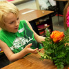 Globe/Roger Nomer<br /> Taddeo Nuse, a third grader at Columbia Elementary, admires his floral work on Friday during a job fair at the school.