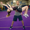 Sean Haase spots a standing back tuck by 14-year-old Maggie Brown, of Carl Junction, during practice at the Flip Shop Cheer Zone in Webb City  on March 16. In addition to coaching the girls, Haase also flies a medical helicopter.<br /> Globe | Laurie Sisk