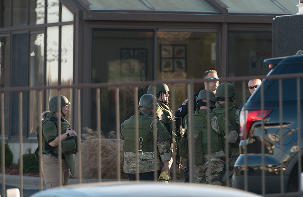 Globe/Roger Nomer<br /> SWAT members gather at the Econo Lodge on Rangeline Road following Wednesday's shooting.