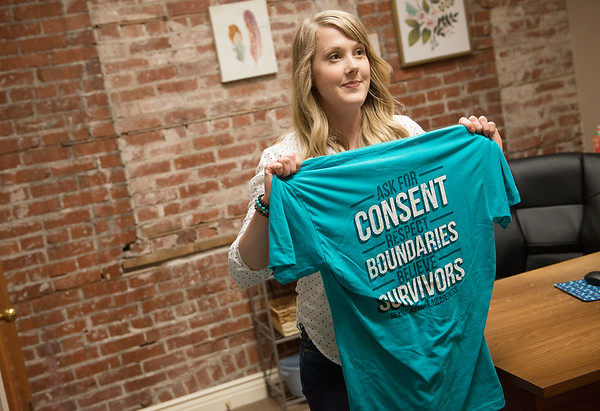 Katy Johnson, development assistant at Lafayette House, displays a printed t-shirt from Lafayette House for Sexual Assualt Awarenesss month on Friday.<br /> Globe | Roger Nomer