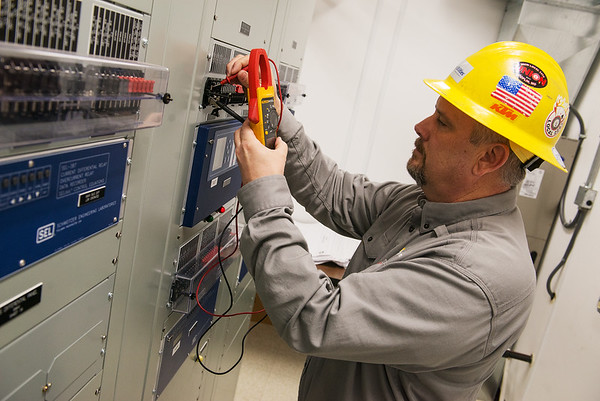 Cody Lee, protection and controls technician with Liberty Utilities Empire District, checks voltage at a substation on Thursday.<br /> Globe | Roger Nomer