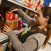 Katie White, freshman at College Heights Christian School, organizes shelves at Crosslines on Wednesday.<br /> Globe | Roger Nomer