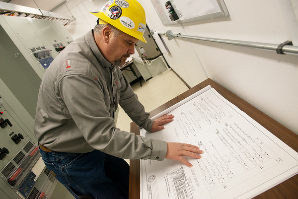 Cody Lee, protection and controls technician for Liberty Utilities Empire District, checks a print at a substation on Thursday.<br /> Globe | Roger Nomer