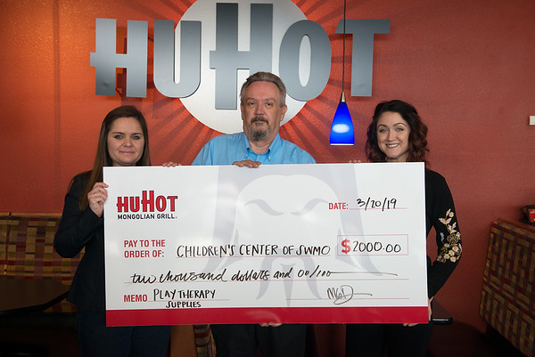 Michael Denson, general manager of HuHot, presents a check for $2,000 to the Children's Center of Southwest Missouri represented by Aryn Crawford, community outreach and development coordinator, left, and Megan Atkins, administrative assistant and events coordinator, on Wednesday at HuHot. The donation came after the restaurant matched its sales on March 11, and acquired additional donations on that day as well. Children's Center will use the donation for play therapy supplies.<br /> Globe   Roger Nomer