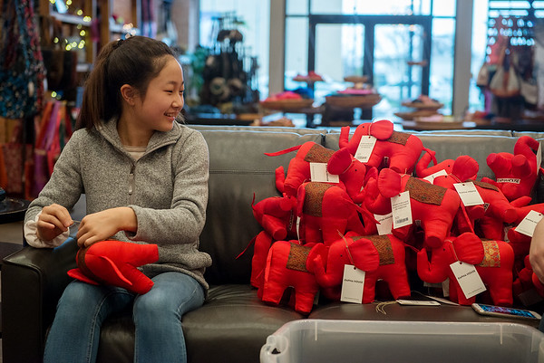 Claire Yi, freshman at College Heights Christian School, tags items on Wednesday at Rapha House.<br /> Globe | Roger Nomer