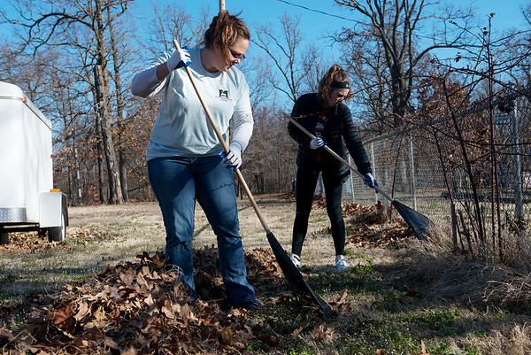 Nicole Hopper and Sydney Newcomb, 15, rake leaves as they volunteer with Habitat for Humanity in Carl Junction on Thursday.<br /> Globe | Roger Nomer