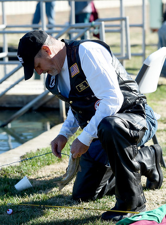 U.S. Navy veteran and former Joplin Postmaster Rodney Bray, of Grove, Okla., removes a rainbow trout from his line during the Rainbows for Vets fishing event on Saturday at the Neosho National Fish Hatchery. Veterans and their families were treated to a Saturday morning of fishing and camaraderie during the event.<br /> Globe   Laurie SIsk