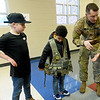 From the left: Columbia fifth grader Taddeo Nuse and second grader Dason Johnson assist U.S. Army Recruiter Sgt. Jeremy Wooten as he details the components of an army fighting load carrier during Career Day on Thursday at Columbia. About 25 presenters from a variety of professions participated in the event.<br /> Globe | Laurie Sisk