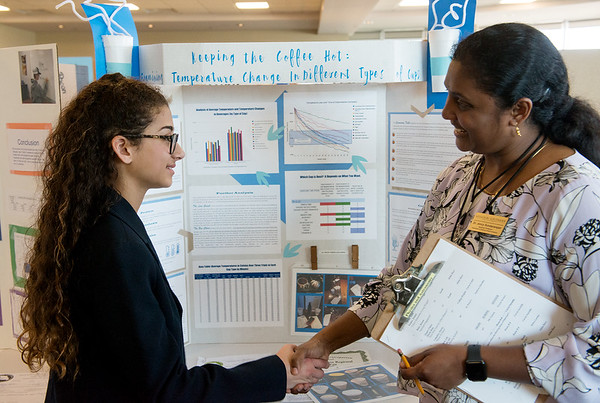 Jency Sundararajan, assistant professor at Missouri Southern, congratulates, Alex Carson, a seventh grader at Joplin South Middle School, on her project on keeping coffee warm during Tuesday's annual Missouri Southern Regional Science Fair at MSSU.<br /> Globe   Roger Nomer