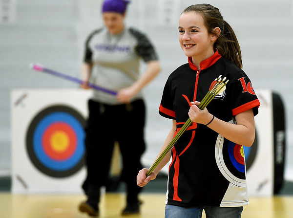 Locust Grove archer Molly Hubbard, 11,  smiles as she reclaims her quivers during the Bullseye competition of the Missouri National Archery in the Schools Program's State Qualifying Tournament on Saturday at Leggett & Platt.<br /> Globe | Laurie Sisk