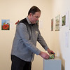 Shaun Conroy, exhibits director for the Spiva Center for the Arts, sets up for the Small Works Auction on Friday.<br /> Globe | Roger Nomer