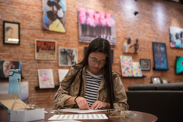 Jaira Glaser, junior at College Heights Christian School, works on tags on Wednesday at Rapha House.<br /> Globe | Roger Nomer