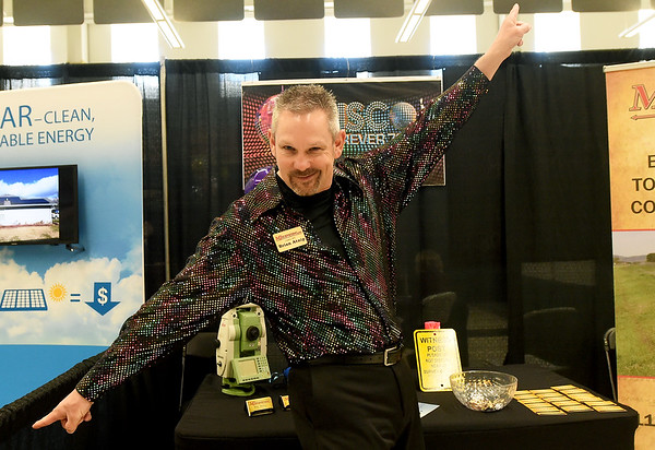 Brian Atnip, of MJ Surveying busts a move during the Neosho Business Expo on Saturday at Neosho High School. The two-day event wrapped up Saturday with its 1970s disco theme as the Neosho Area Chamber of Commerce celebrated its 70th anniversary.<br /> Globe | Laurie SIsk